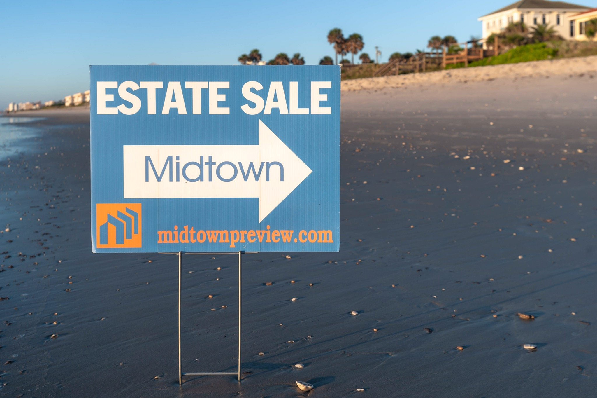A Midtown Estate Sale street sign placed in the golden sands of a Melbourne Florida beach